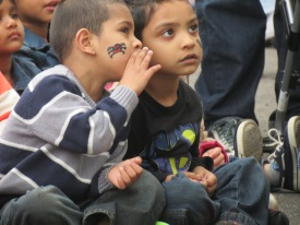 A secret is shared as two boys watch a magician at a fall festival in Woodhaven, Queens.