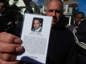 Raul Marroquin holds the prayer card for Jose Robles, who he grew up with and considered to be like a brother. Marroquin and others were attending a wake for Robles when gunfire erupted outside the church, killing two people.